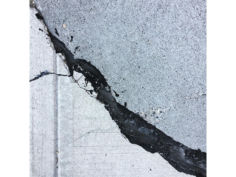 A photo of two different types of concrete connected with tar on a sidewalk