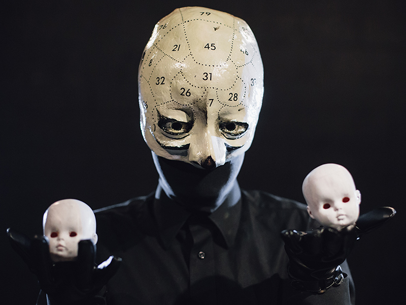 A creepy figure in a mask holds two pale, white and bald dolls