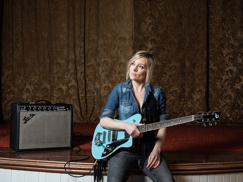 A promo photo of Christina Martin sitting on stage with a teal guitar and an amp