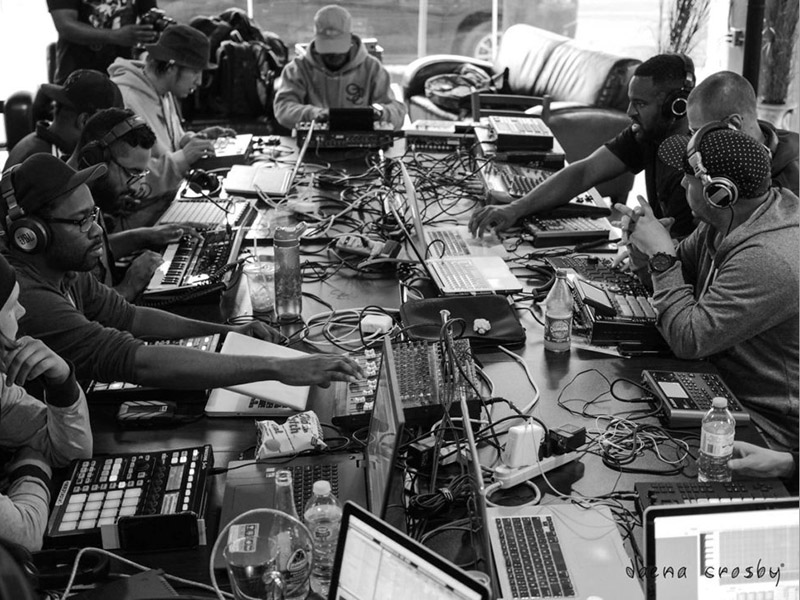 A black and white photo of a group of people and all their music equipment on a table
