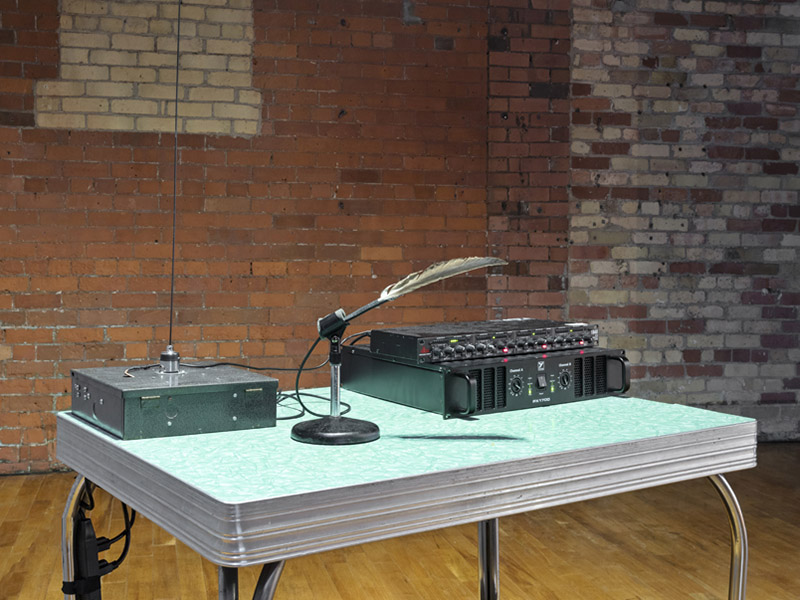 Recording equipment sits on a blue laminate table top in front of a brick wall