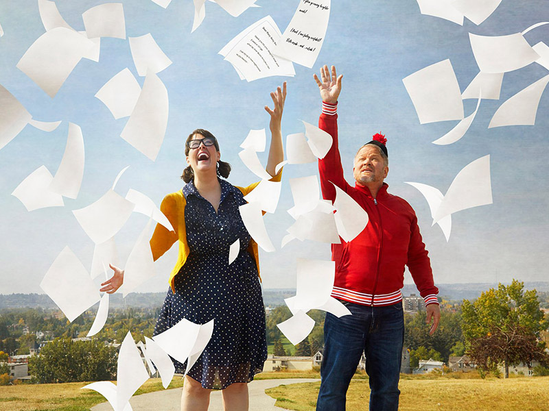 A girl and a man throw letters into the air