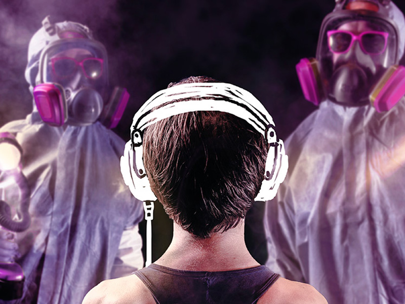 A person with headphones looks towards two people unrecognizable in paint masks and smocks