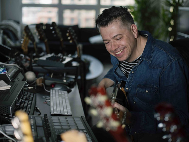 A photo of Russell Broom holding a guitar at a mixing table