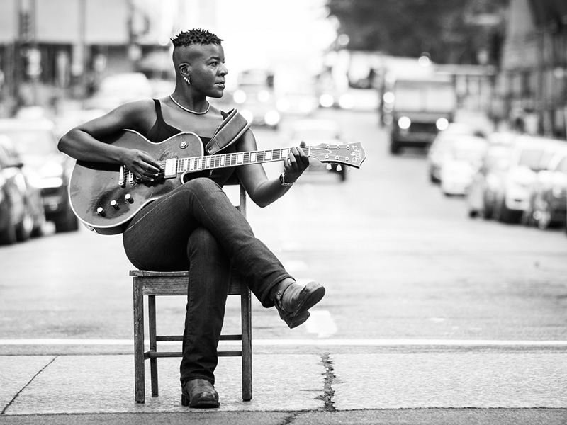 A promo photo of Cécile Doo-Kingué holding a guitar in the middle of a street