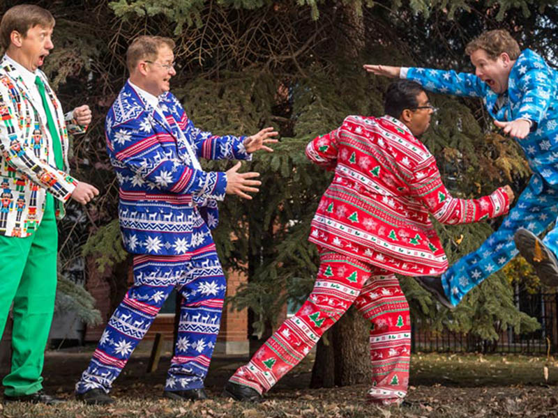 The Heebee-jeebees mock fight while wearing colourful Christmas suits