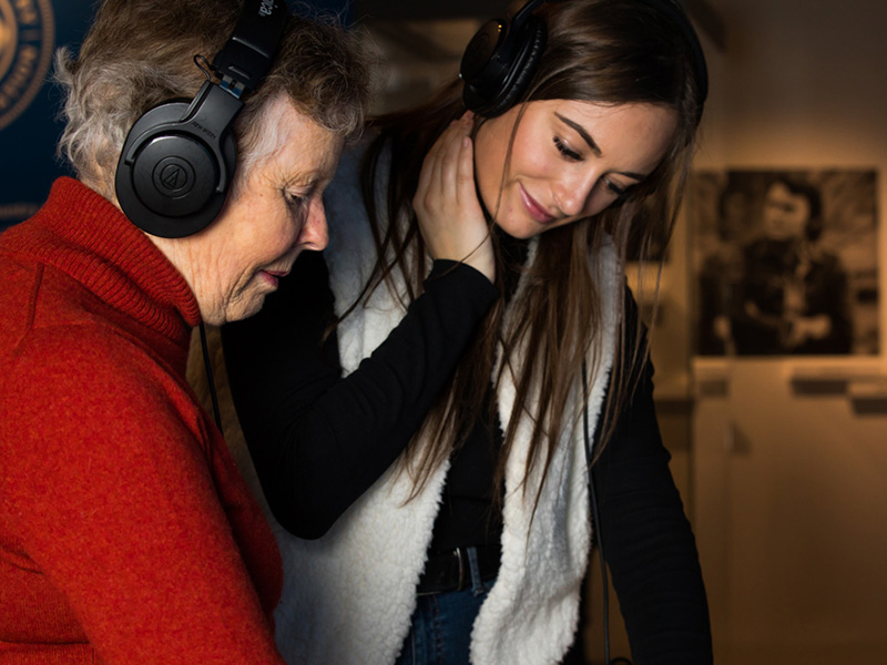 Two generations listen to an interactivity at Studio Bell