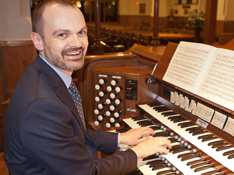 A photo of Neil Cockburn at the keyboard of an organ