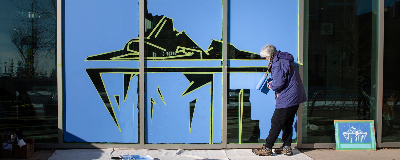Barbara Amos paints an iceberg on a window at Mount Royal University