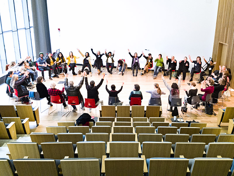 A circle of participants move along to instructions in the Performance Hall of the new Central Library