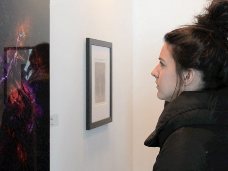 A person looks at pieces on display at Exposure HQ at the 2018 Exposure Photography Festival