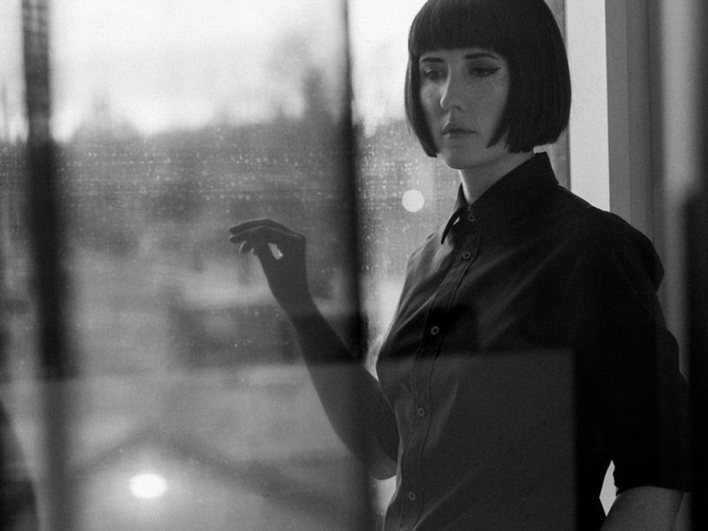 A photo of Ellen Doty through a relective window