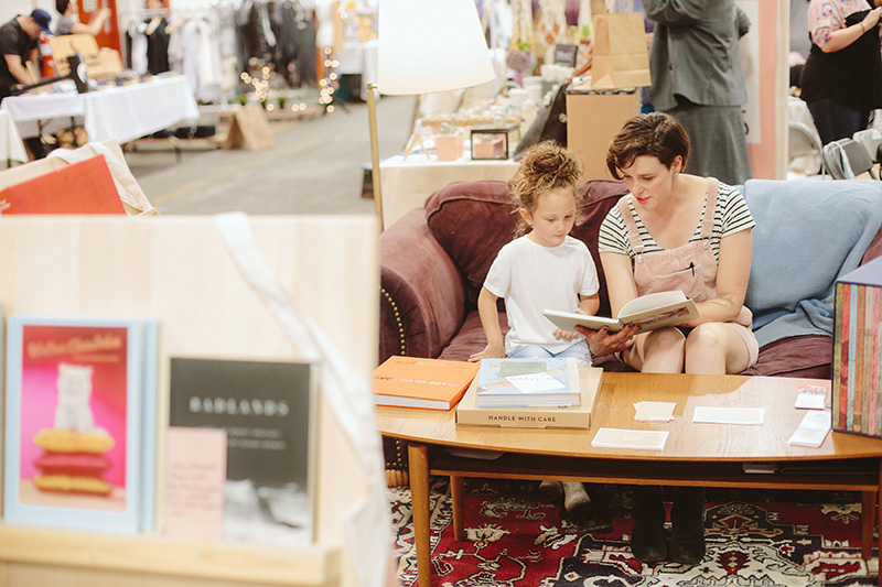 A woman reads to a child at Market Collective's MC9Year event