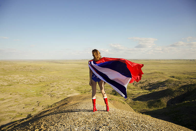 A photo of a woman standing on the prarie wearing a cape