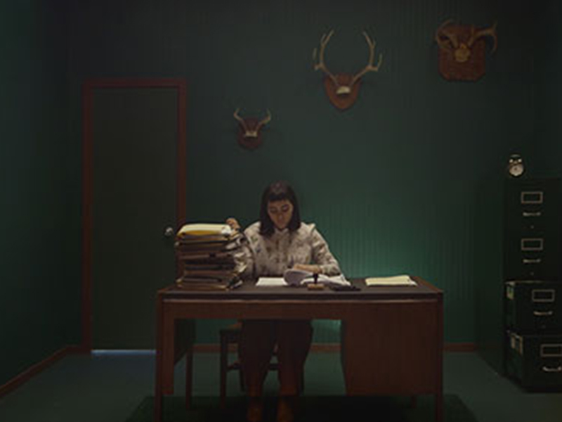 A still from Carol Nguyen's Facade, a person sits at a dimly lit desk with piles of paperwork