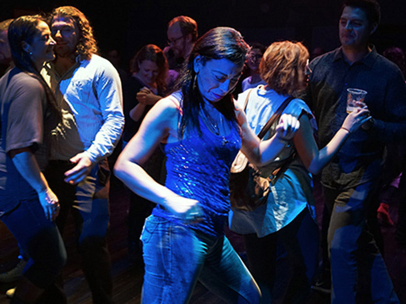 Writer, performer, and activist Carmen Aguirre dances in a crowd
