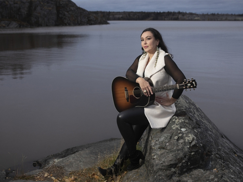 Leela Gilday holds a guitar while sitting next to a pristine lake