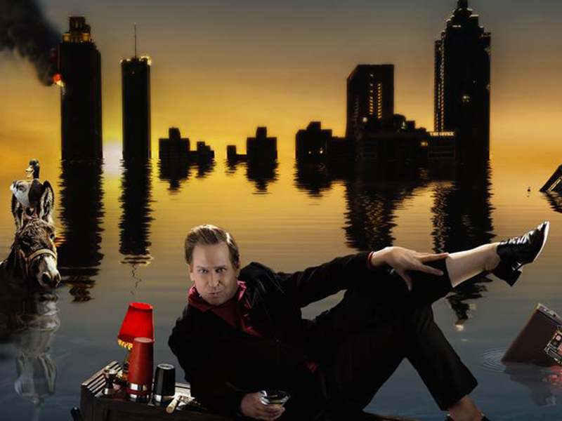 A graphic of Buddy Cole lounging in front of a flooded skyline
