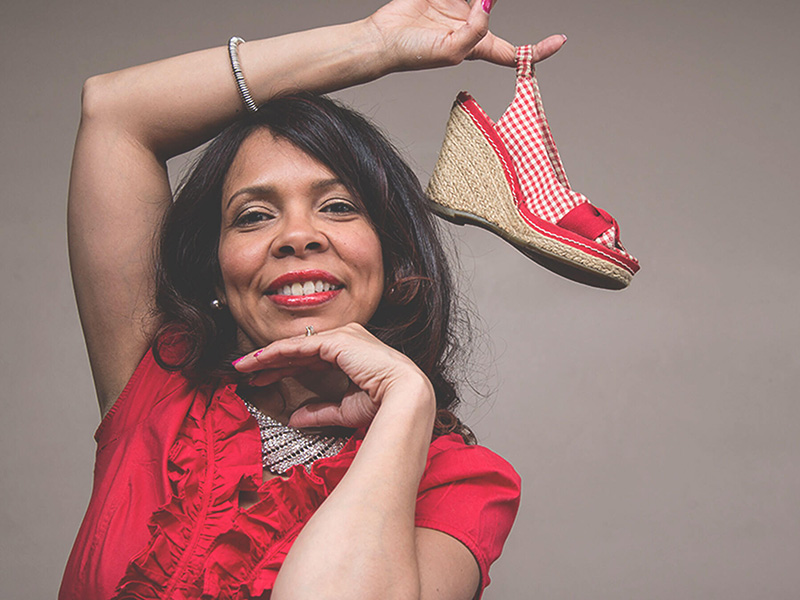 A woman smiles and holds a shoe