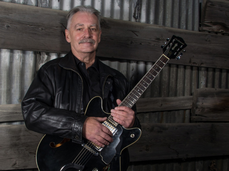 A photo of Thomas T Blues holding a guitar