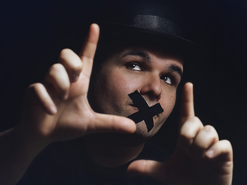Javier Vilalta performing with electrical tape over his mouth