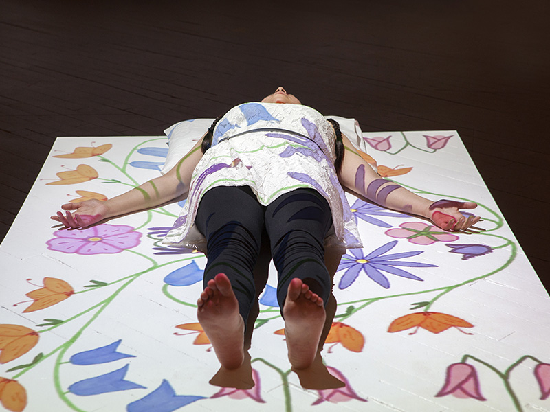 Jessica McMann laying on a sheet with flowers painted over her and it