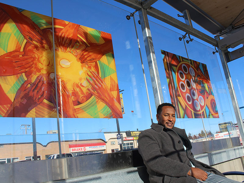 Sisay Shimeles sits in front of his work in the International Avenue BRT shelter adjacent to 52nd St. SE