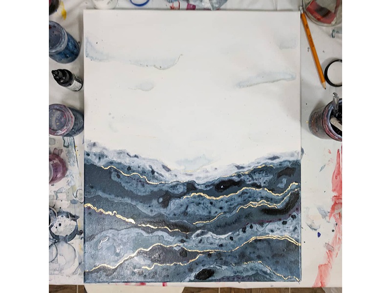 A photo of a painting sitting on a work top with tools surrounding it