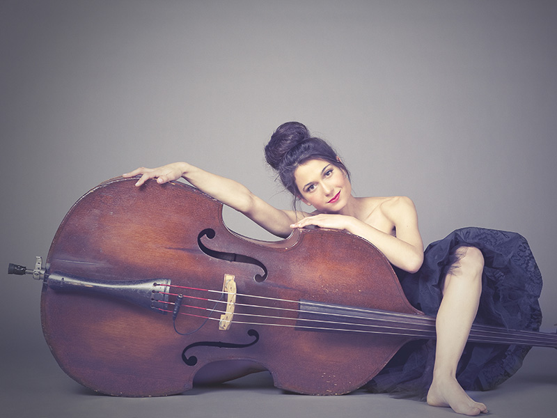 A photo of Brandi Disterheft leaning on her bass