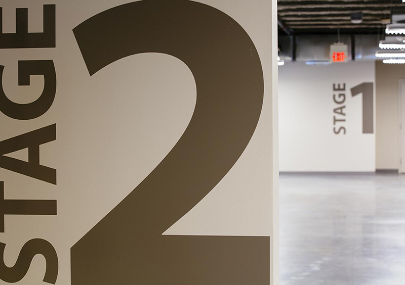 Stage 2 and Stage 1 can be seen in a Calgary Film Centre hallway
