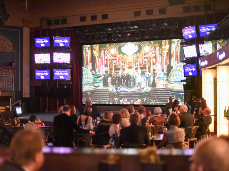 The audience watches a live stream of the Oscars at The Palace Theatre for A Red Carpet Affair