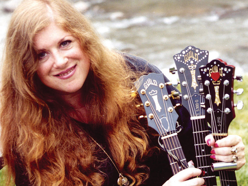 A photo of Ellen McIlwaine holding three guitars