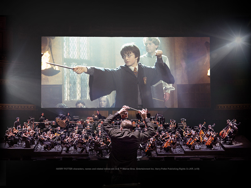 An orchestra plays in front of a screening of Harry Potter and the Chamber of Secrets