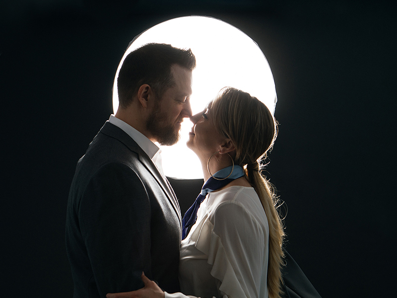 A couple leans in to kiss in front of a bright, round light