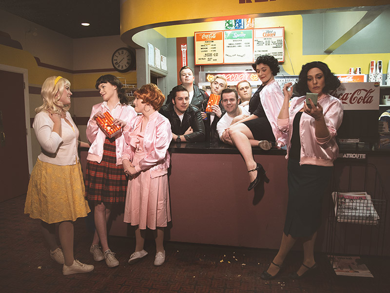 The cast of Front Row Centre's production of Grease stand around the concession at The Plaza Theatre