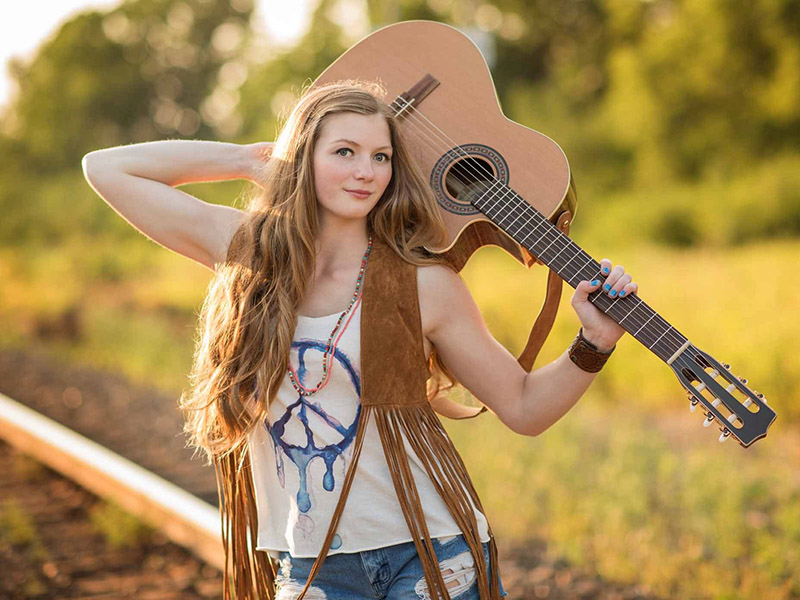 A promo photo of Rebecca Lappa holding a guitar on a railway track