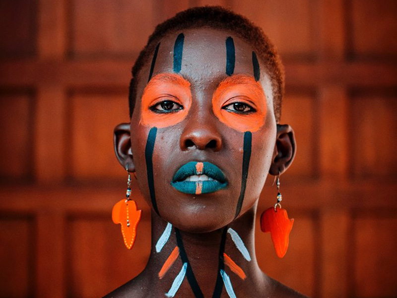 A performer wearing face paint and earrings shaped as Africa