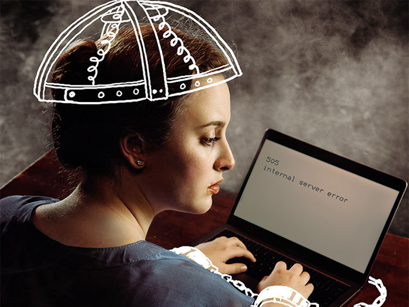 A woman is cuffed to a laptop and wearing a cap from an electric chair