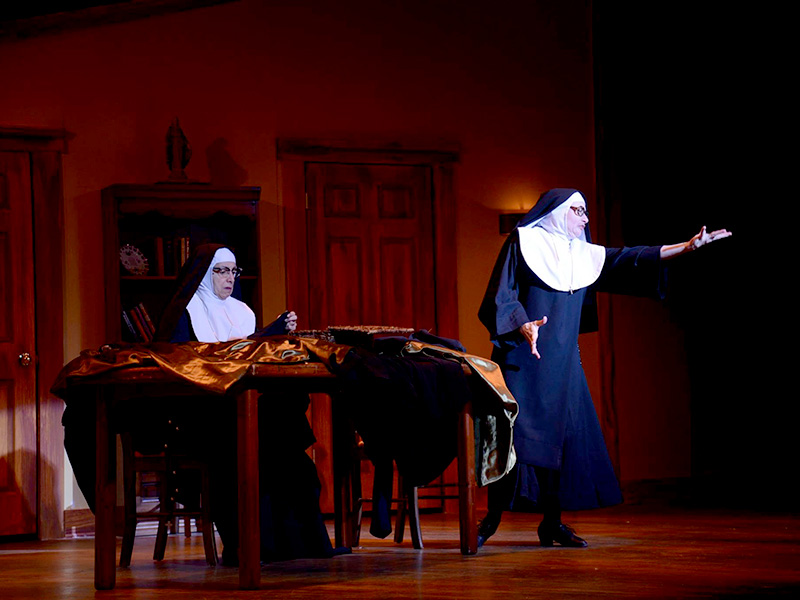 One nun sews while another emotes on stage