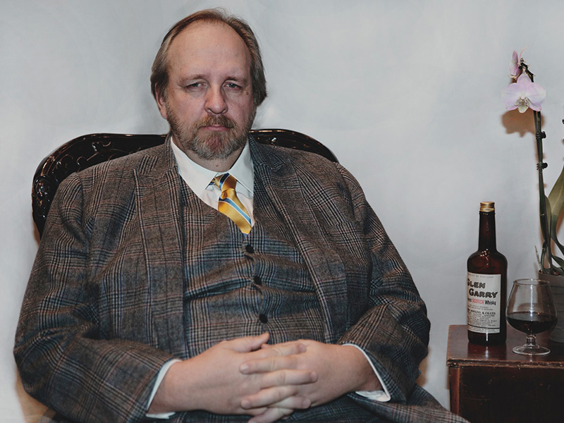 Nero Wolfe sits next to a booze bottle and an orchid