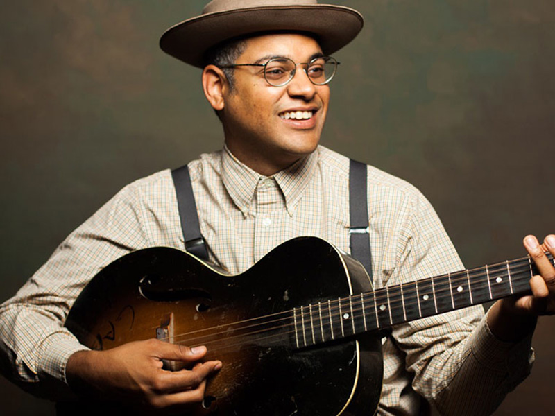 A promotional photo of Dom Flemons holding his guitar