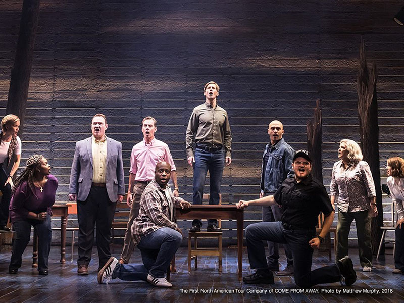 The cast of Come From Away on stage singing