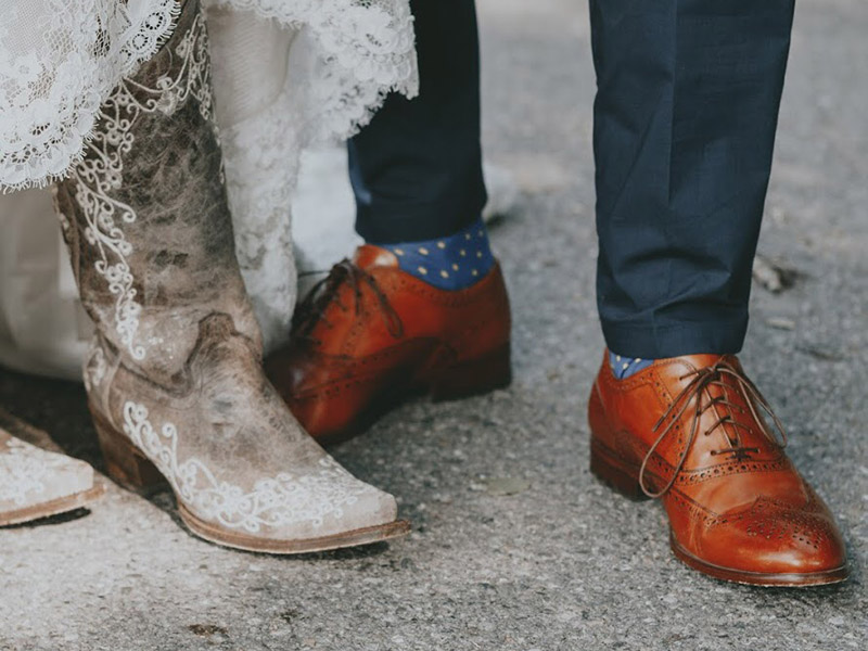 Two people wearing fancy shoes, distressed white cowboy boots and brown loafers