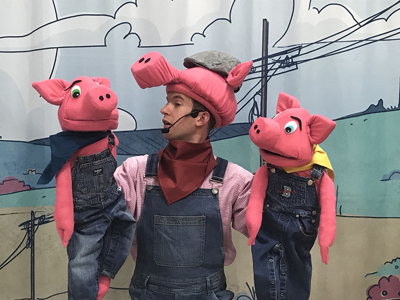 A puppeteer controls two pigs in Evergreen Theatre's production of The Three Little Pigs and B.B. Wolfe