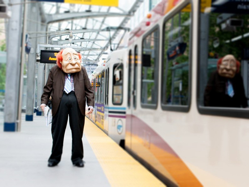 A puppet fellow waits on the CTrain platform as a train goes by