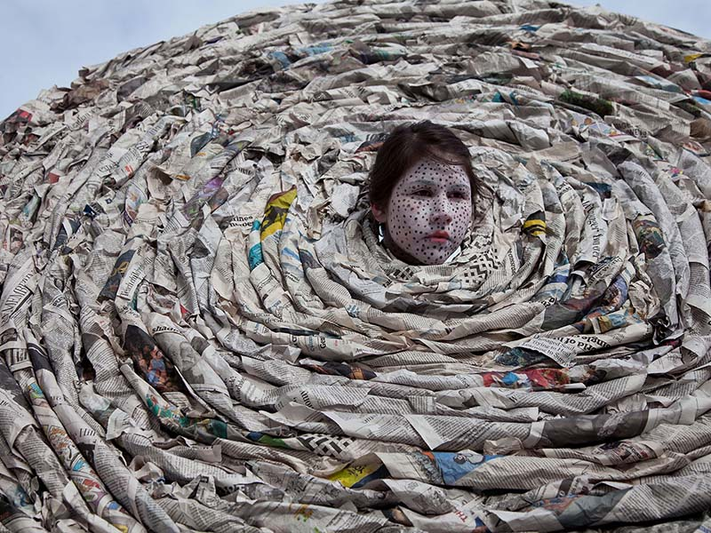 Meryl McMaster's head pokes out of a cirlce of newspaper