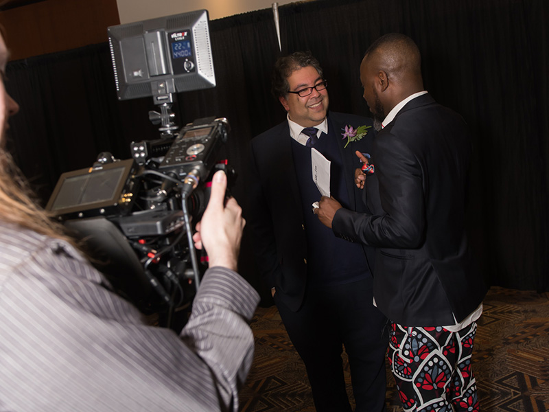 A behind-the-scenes photo showing Lanre Ajayi interviewing Mayor Naheed Nenshi