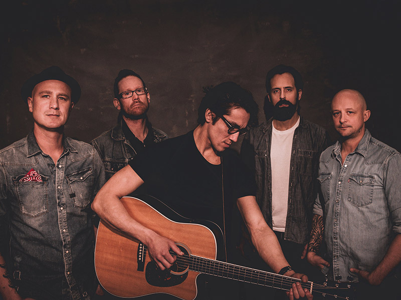 A promotional image of The Prairie States with one band member holding an acoustic guitar