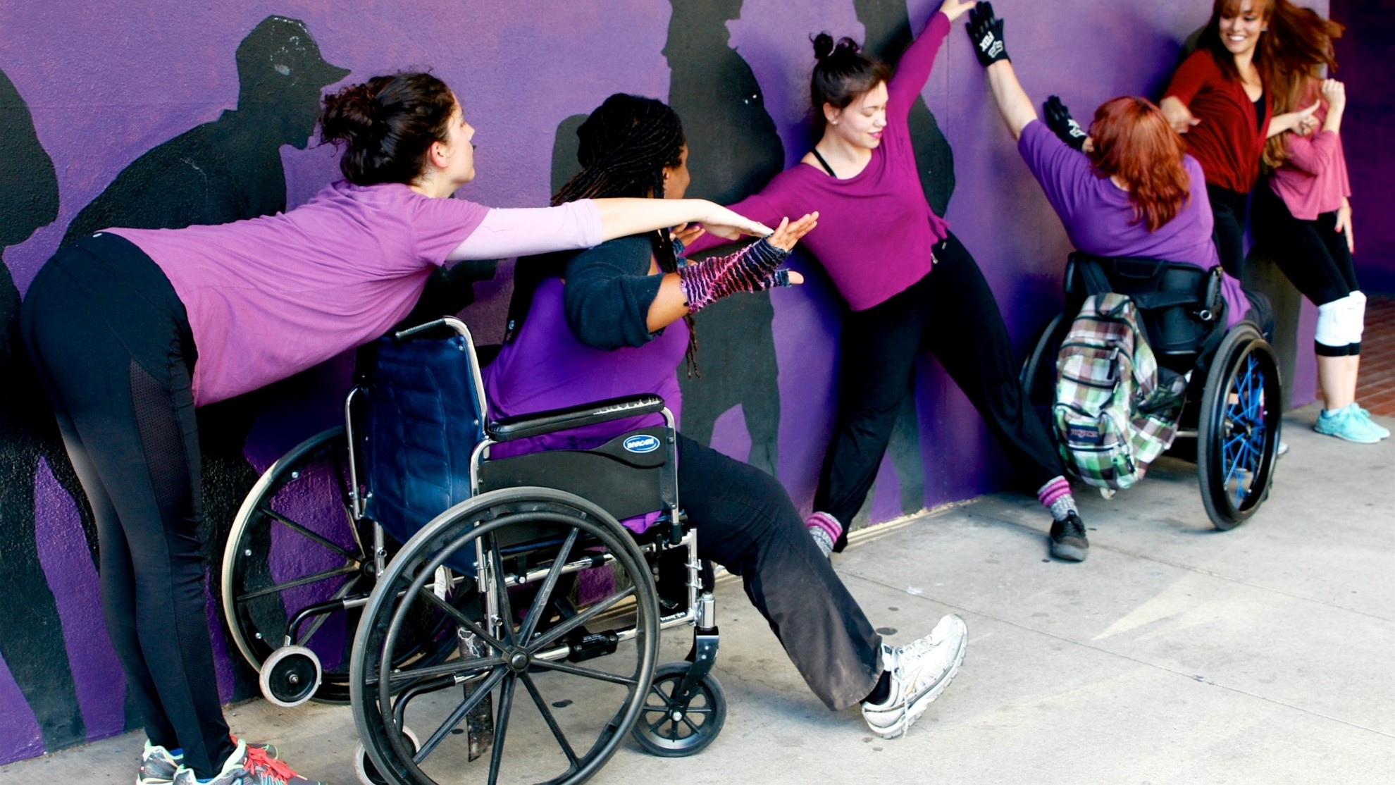 A group of dancers in wheelchairs and wearing knee pads