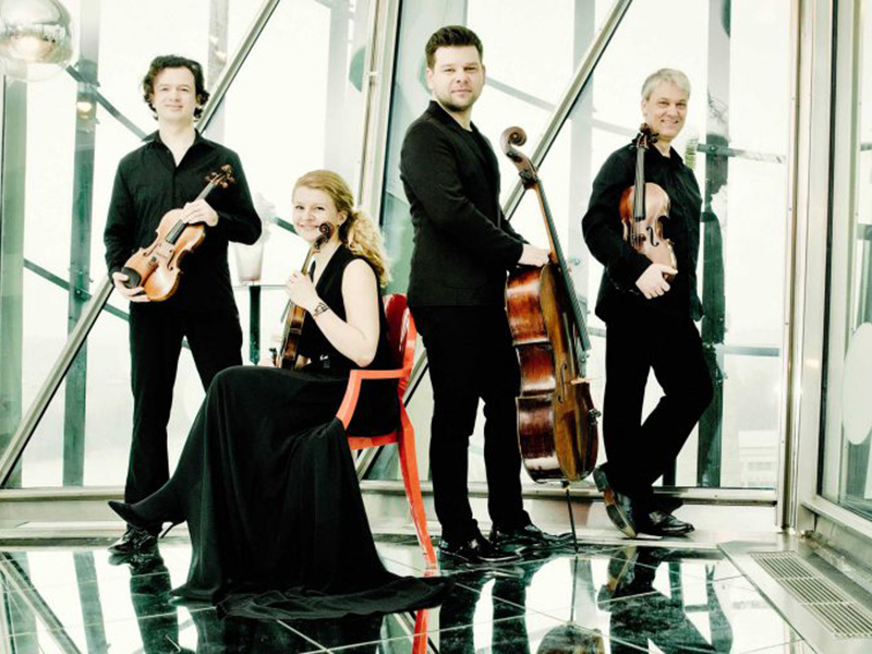 A promotional photo of the Pavel Haas Quartet with their instruments